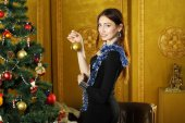 Brunette girl decorates the Christmas tree. — Stock Photo