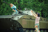 Mother and son at military vehicle. — Stock Photo