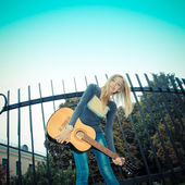 Girl in city park with guitar — Stock Photo