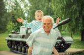 Grandfather and grandson near tank — Stock Photo