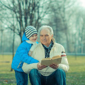 Grandfather and grandson reading a book — Stock Photo