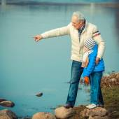 Grandfather and grandson on the river stones — Stock Photo