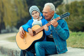 Grandfather and grandson playing guitar — Stock Photo