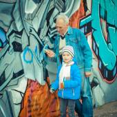 Grandfather and grandson paint graffiti — Stock Photo