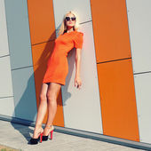Fashion girl in sunglasses and orange dress — Stock Photo