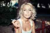 Kvinna på en bänk och röka cigarr — Stockfoto