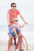 Family biking at the beach — Stock Photo