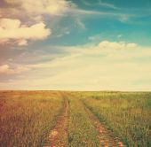 Road in fields and cloudy sky — Stock Photo