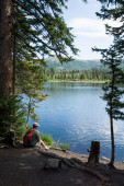 Man with a backpack admiring alpine lake. — Stock Photo