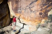 Boy shows his hand on the wall with petroglyphs. — Stock Photo