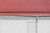Rain gutter and red tiled roof — Stock Photo