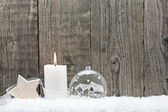 Christmas bauble in snow against wooden boards — Stock Photo