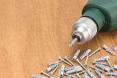 Drill and screws on wooden table — Stock Photo