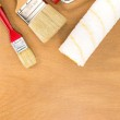 Paint roller tray with brushes on wooden surface — Stock Photo #72490637