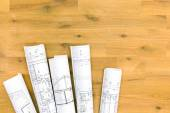Rolls of architectural blueprints on wooden table — Stock Photo