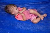 Little baby girl asleep outdoors on a hammock — Stockfoto