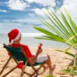 Man in Santa's hat with cocktail sitting on chair on a beach — Stock Photo #65437901