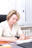 Mid-life business woman write document — Stock Photo