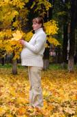 Pregnant woman in autumn park hold maple leaf — Stock Photo
