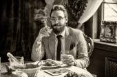 Man with a beard and mustache, smoking a cigar during dinner — Stock Photo