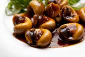 Snails cooked in tamarind sauce with herbs on a plate — Stock Photo