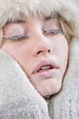 Very cold weather. Chilled female face covered in ice. — Stock Photo