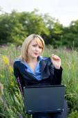 Contented businesswoman with pedicle in a mouth sitting on grass — Stock Photo