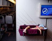 Small two year old baby girl sleep in a bassinet on a airplane — Stock Photo