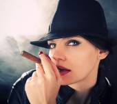 Attractive brunette in a felt hat smoking a cuban cigar — Stock Photo