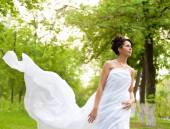 Young white dressed woman walking in spring park — Foto Stock