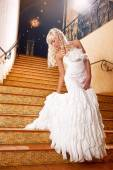 Beautiful girl in a wedding dress going down the stairs — Stock Photo