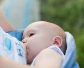 Mother breast feeding her infant in sling — Stock Photo