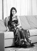 Attractive smiling sexy girl sitting on sofa — Zdjęcie stockowe
