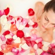 Attractive naked girl enjoys a bath with milk and rose petals — Stock Photo #65667549