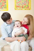 Young happy family sitting on sofa at home — Stock Photo