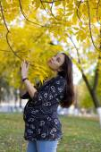 Pregnant woman in autumn park hold the limb — Stock Photo