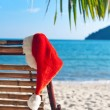 Red Santa's hat hanging on beach chair under palm tree — Stock Photo #65696987
