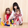 Mother and daughters play with bright geometric toys — Stock Photo #65697761
