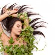 Young beautiful nude woman with green ivy leaves wrapped around — Stock Photo #65698365
