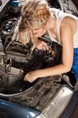 Girl tries to repair broken car — Stock Photo