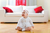 Happy baby girl seated on a hardwood floor — Stock Photo
