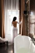 Beautiful woman open the curtain — Stock Photo