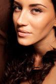 Portret van mooie jonge brunette vrouw met krullend haar — Stockfoto
