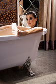 Woman is sitting in bath and have videochat by smartphone — Stock Photo