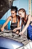Two female auto mechanic repairing a car — Stock Photo