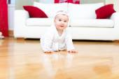 Happy eight month old baby girl crawling on a hardwood floor — Stock Photo