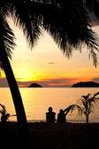 Силуэт романтичной пары, сидя на пляже на закате — Стоковое фото