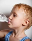 Quench thirst. The boy is drinking mineral water from bottle — Stock Photo
