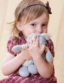 Little girl clasp toy rabbit to one's bosom — Stock Photo