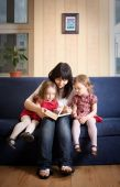 Mother reading a book to her little daughters — Stock Photo